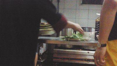7月23日,汉丽轩烤肉超市昌平店,服务员将几盘顾客剩菜(左手中叠在一起的是几盘肉,其右手正整理韭菜)端回后厨,进行整理后准备再送往餐厅自助取餐区供顾客食用。
