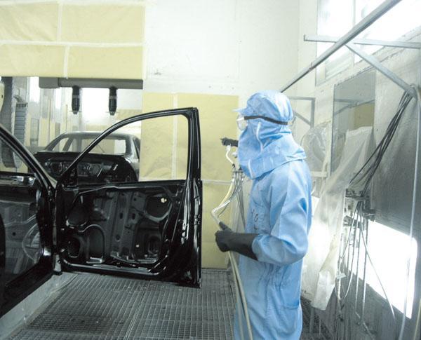 汽车涂装车间生产工人穿着防静电连体服正在工作